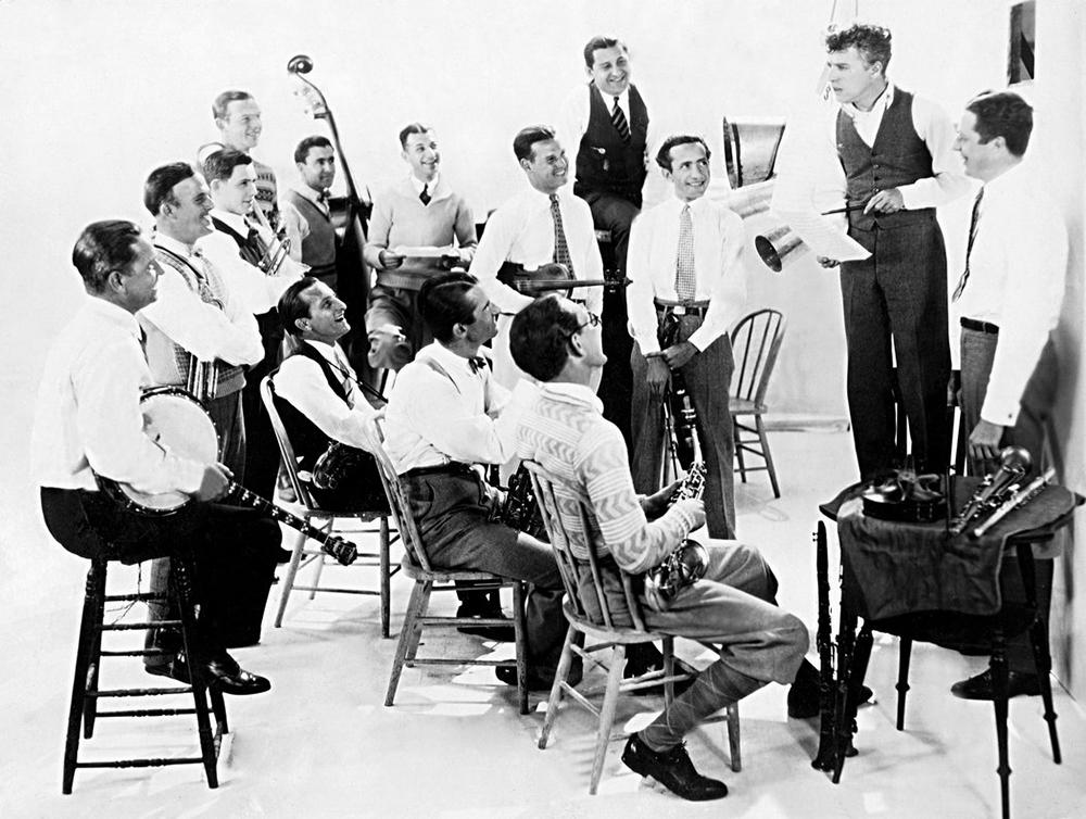 Чарли Чаплин (стоит на стуле) обсуждает с участниками оркестра California-Brunswick Orchestra композиции к фильму «Золотая лихорадка», 1925 год/ Фото: Everett Collection/ Фото с сайта nytimes.com